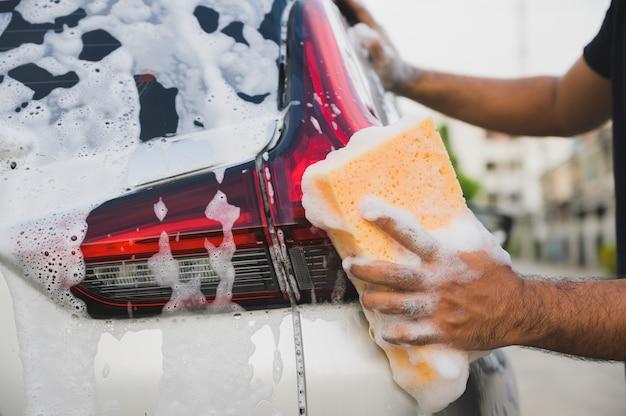 スポンジで車を掃除する男