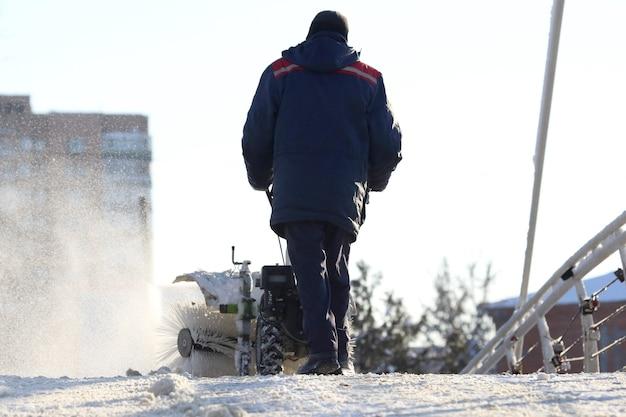 Человек чистит улицу от снега ручной трактор специальный