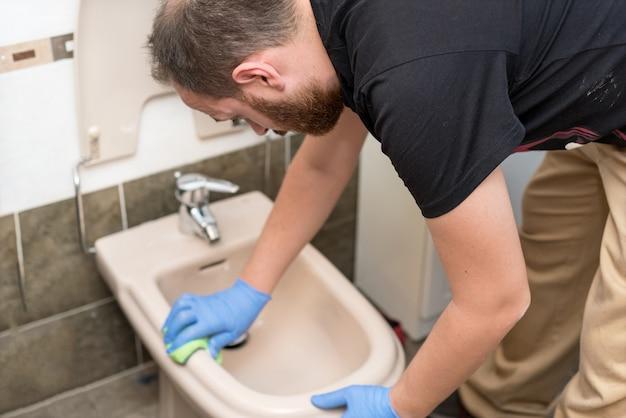 Man cleaning toilet bidet