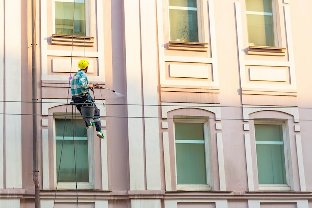 Man cleaning windows and wall on old city bulding