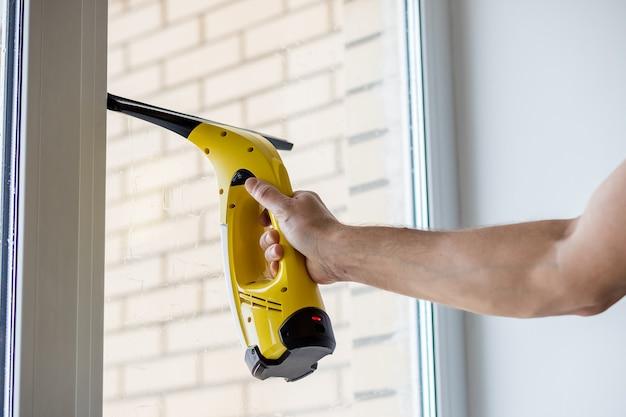 Человек чистит окна пылесосом