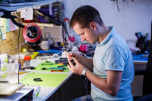 Человек очищает ноутбук с помощью специального инструмента от пыли. ремонт и обслуживание ноутбуков и пк рекламные услуги по ремонту электроники и устройств.