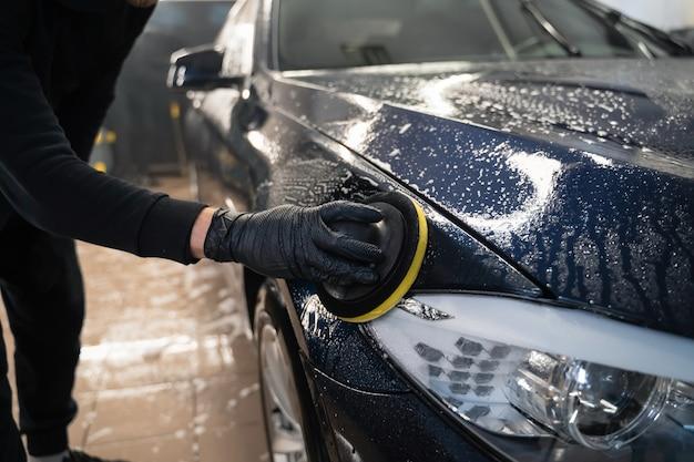 Человек чистит кузов автомобиля круговой губкой.