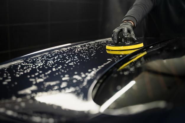 Мужчина чистит капот машины круговой губкой.