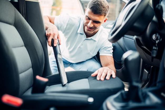 Мужчина чистит салон автомобиля пылесосом на автомойке. мойка автомобилей