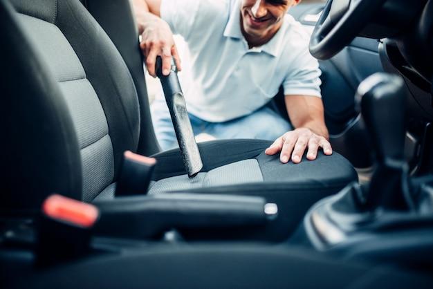 Мужчина чистит салон автомобиля пылесосом
