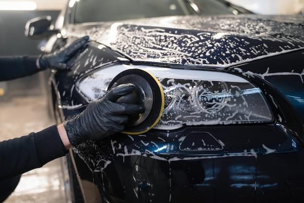 Человек чистит автомобильную лампу круговой губкой. подготовка авто к полировке.