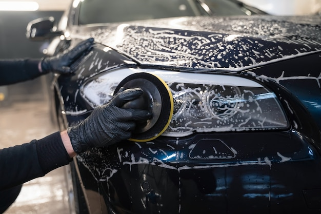 Man cleans car lamp with circle sponge. preparing auto for polishing.