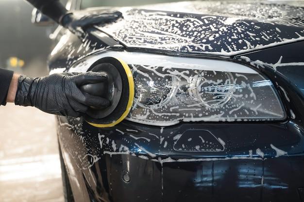 Человек чистит автомобильную лампу круговой губкой.