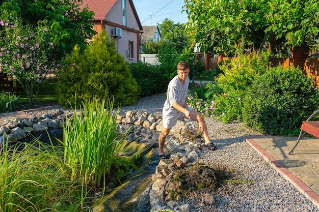 남자는 진흙 슬러지와 수생 식물에서 정원 연못 바닥 착륙장을 청소합니다