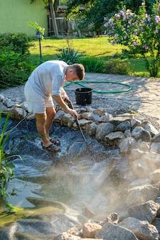 남자는 진흙과 슬러지에서 고압 세척기로 정원 연못 바닥을 청소합니다