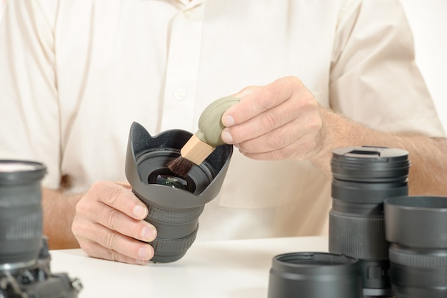 Man cleans the lens from accumulated dust