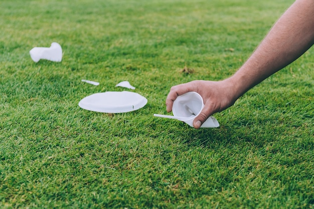 Мужчина убирает с природы пластиковый мусор