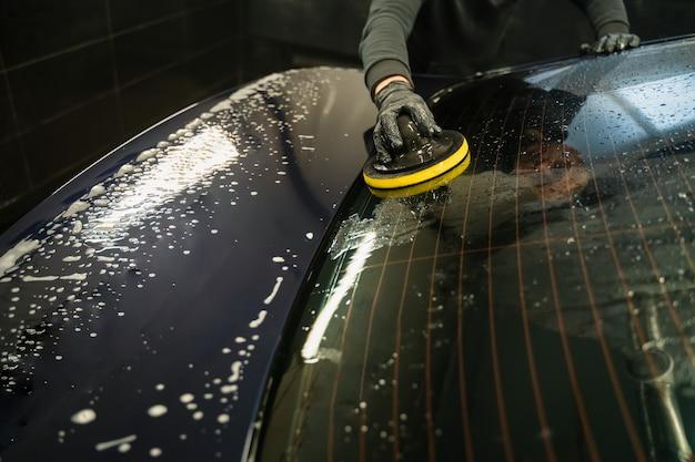 Мужчина чистит заднее стекло автомобиля губкой.