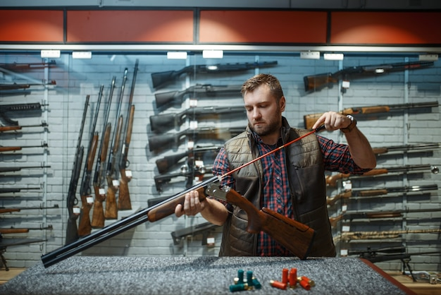 Man cleans rifle barrel at counter in gun shop. equipment for hunters on stand in weapon store, hunting and sport shooting hobby