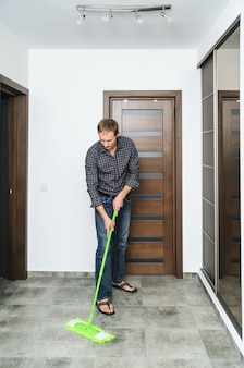 The man cleans the room.