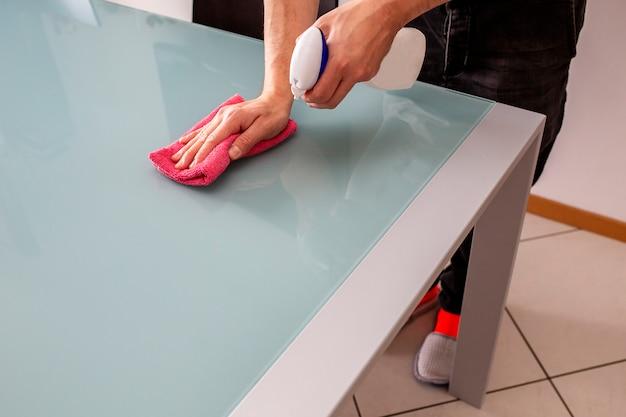 Человек очищает стол в гостиной с помощью спрея моющего средства и ткани.