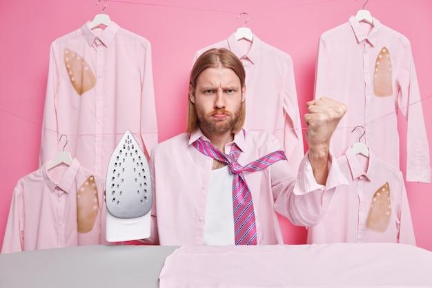 Мужчина сжимает кулак, с сварливым выражением лица, одетый в формальную одежду, занят глажкой во время выходных, стоит в прачечной возле доски. концепция работы по дому