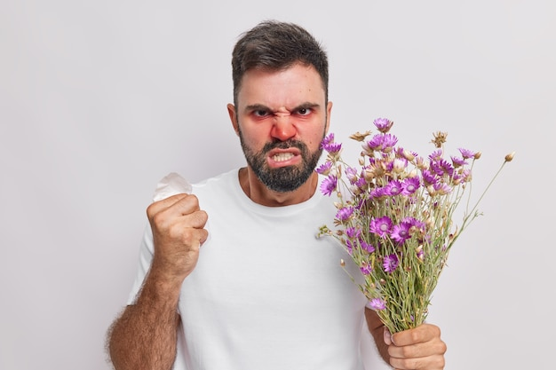 Man clenches fist and teeth looks outraged suffers from seasonal allergy has red runny nose and swollen eyes holds napkin allergic to wildflowers. healthy problems