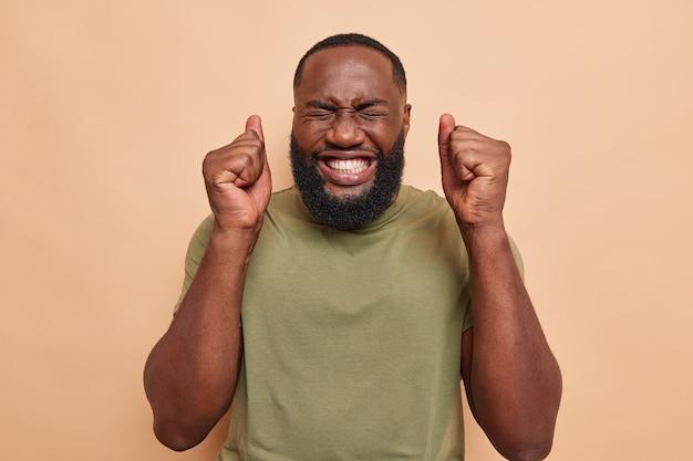 Мужчина с успехом сжимает кулаки, празднует триумф с закрытыми глазами, зубасто улыбается, одетый в повседневную футболку на бежевом