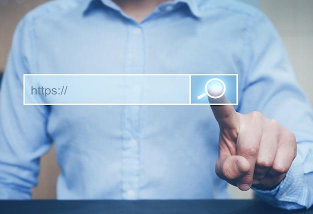コンピューターのタッチスクリーンでインターネット検索ページをクリックする男。