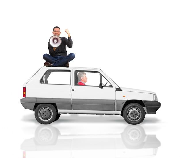 남자는 확성기를 통해 소리와 주먹을 올리는 동안 자동차의 지붕에 올라
