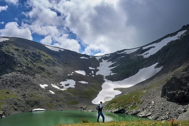 A man, a climber with a backpack, climbs the peak of a mountain near a blue lake. altai