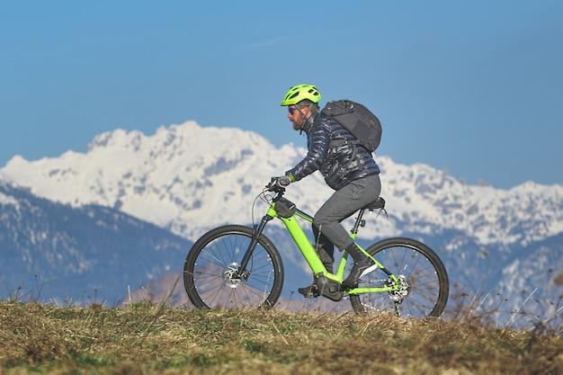 マウンテンバイクで山の牧草地を登る男
