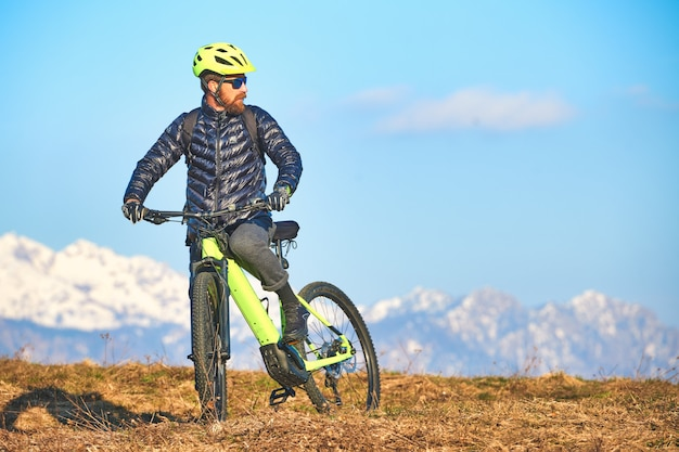 Man climbing a mountain meadow with mountain bike