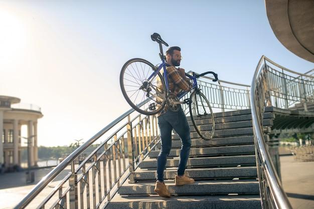 彼の肩に自転車で階段を登る男