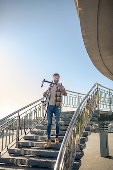 Man climbing stairs with a bike on his shoulders