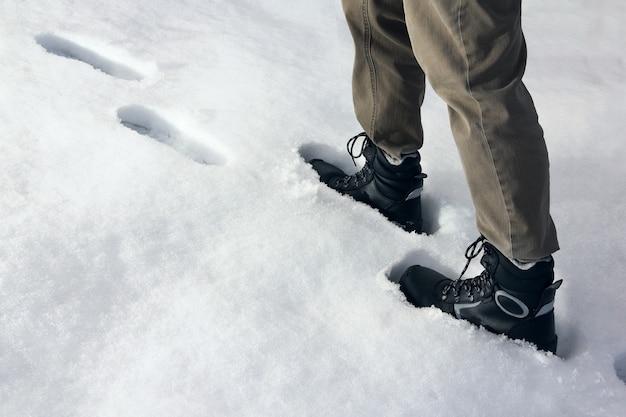 Человек поднимается по снежному склону, следуя по стопам других