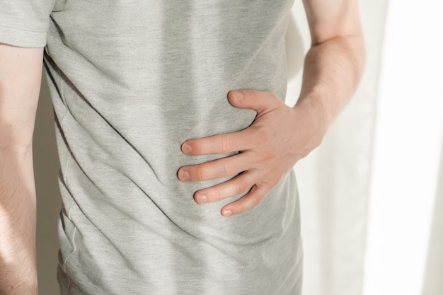 A man clings to his stomach with his hands. the man got a stomachache. belly close up