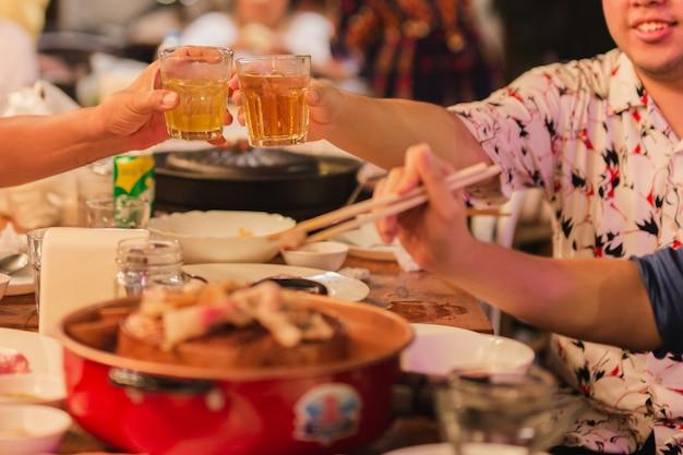 男が家族との夕食を祝うアルコールでガラスをチャリンという音します。