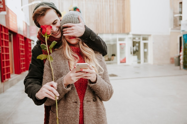 Man closing eyes to girlfriend and giving rose