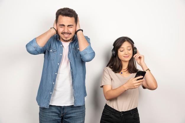 여자 시끄러운 음악을 듣는 동안 그의 귀를 닫는 남자.
