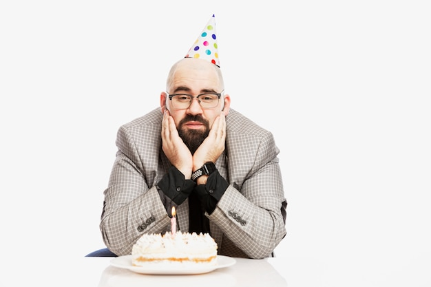 A man in a clown hat is sitting in front of a cake with a candle. sad birthday. white wall.