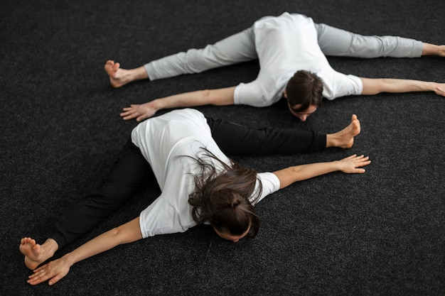 Man coach and woman are doing stretching in the gym. two people do yoga. concept healthy and athletic lifestyle.