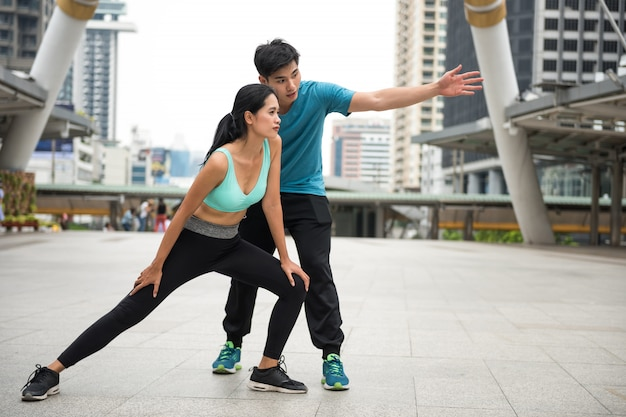 Man coach woman to stretching before running