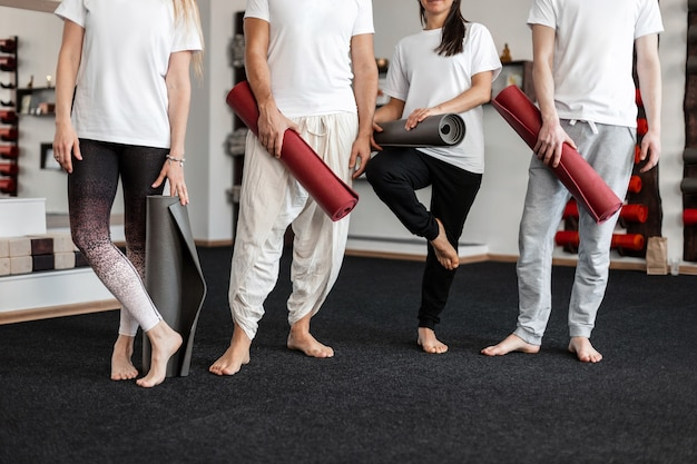 Man coach and women are standing with modern gym mats in hands in a fitness studio. group stretching, pilates or yoga training. close-up.