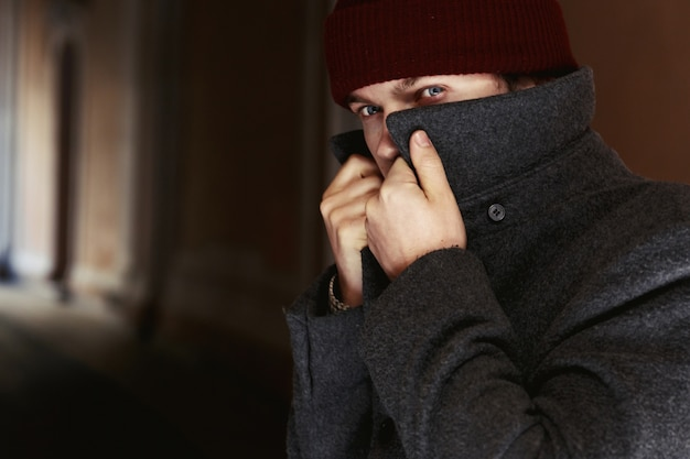 Man in a coat hides his face behind tall collar