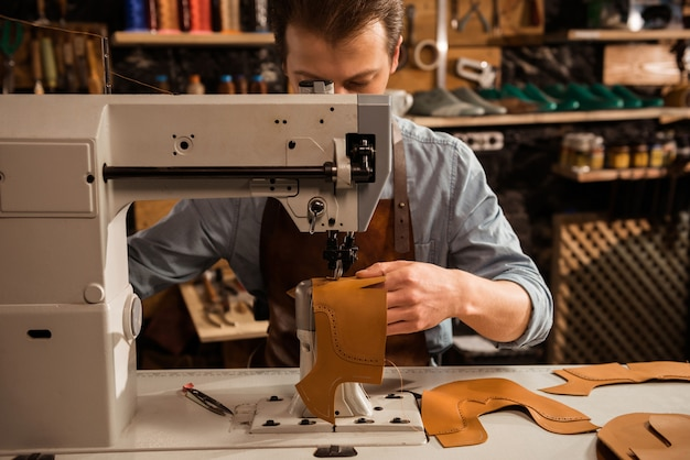 Man cobbler stitching leather patrs