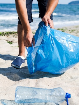 Man collecting plastic trash from the beach and putting it into blue garbage bags for recycle