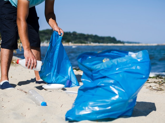 Man collecting waste plastic trash from the beach and putting it into blue garbage bag