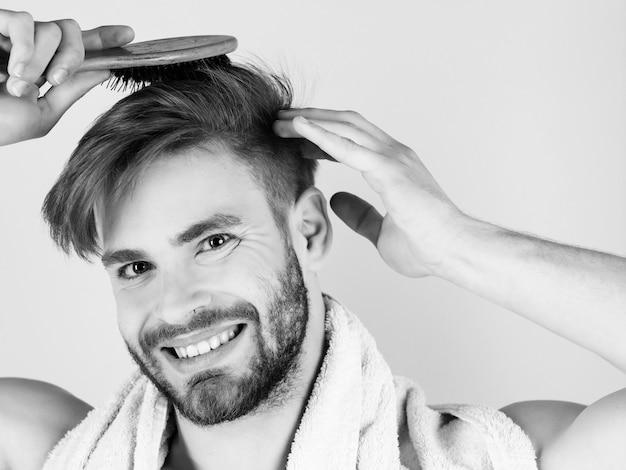強い腕のブラシで健康な髪をとかす男