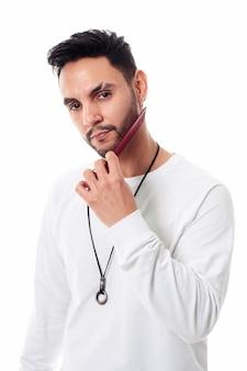 흰색 바탕에 그의 수염을 빗질하는 남자