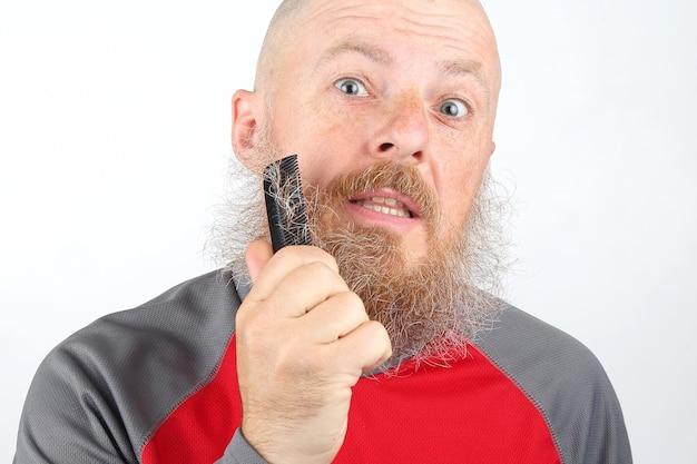 男は彼のひげを櫛でとかす