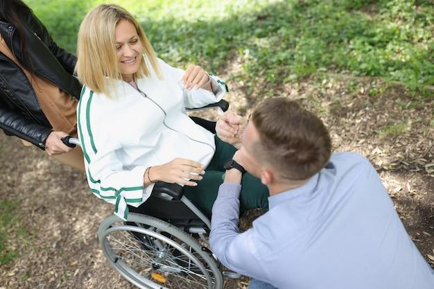 男性は、公園のサポートで椅子に座っている障害のある女性の笑顔と通信します