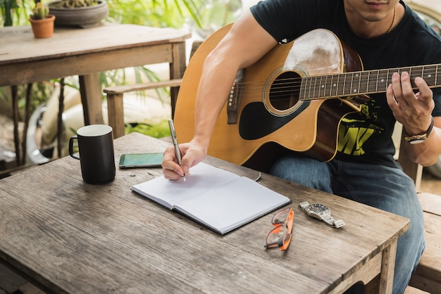 Man compose song and play guitar