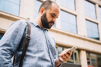 Man concentrated on smartphone at street